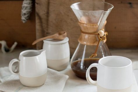 A Chemex sits atop a table with a linen napkin and mug, perfect for how to make coffee at home.