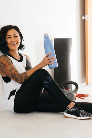 A woman sitting down on the floor drinking water after a workout. What to eat after a workout.